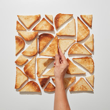 The Hand Of The Girl Makes A Pattern Of Square-shaped Pieces Of Fried Toast On A Gray Background. Flat Lay