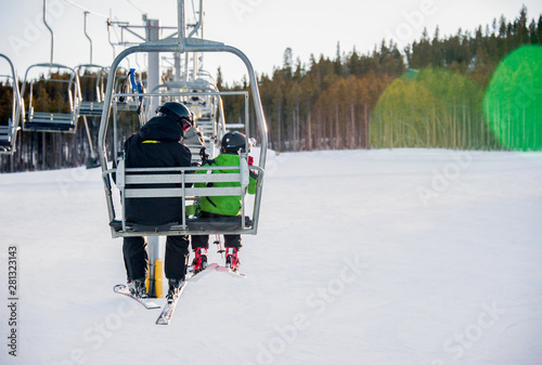 Father and son sitting together on chairlift in winter