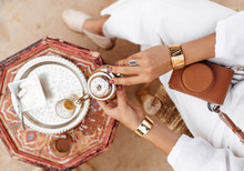 Female Hands With Rings And Bracelets Holding A Pot Of Tea