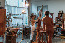 Woman Painting Model On Canvas At Her Studio