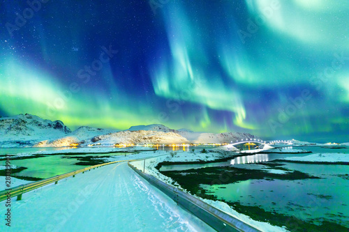 Poster Aurore polaire Amazing view on natural wonder Northern Lights or Aurora Borealis over lighting Kubholmenleia bridge crossing the fjord. Lofoten Islands Archipelago in Norway, location over Polar Circle.