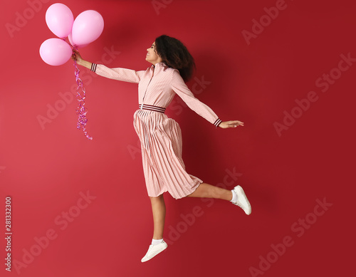 Portrait of jumping African-American woman with air balloons on color background Tapéta, Fotótapéta