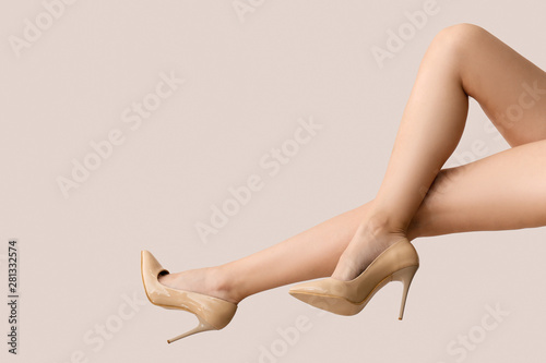 Foto Legs of young woman in high-heeled shoes on light background