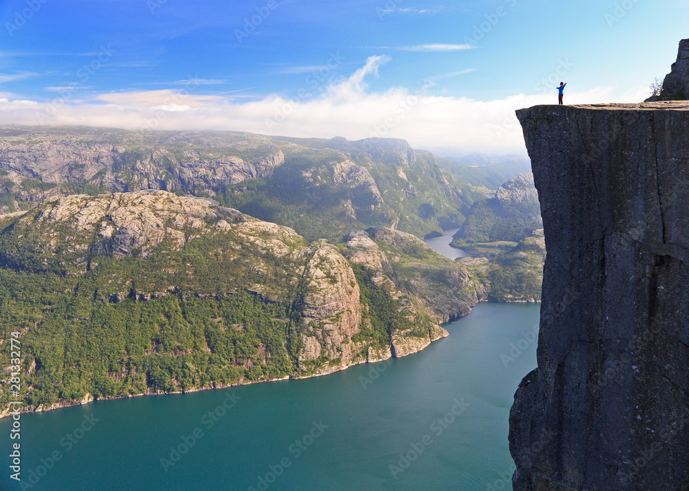Fototapeta Scenic view of a hiker standing on Preikestolen (Pulpit Rock) and looking on the fjord, Norway