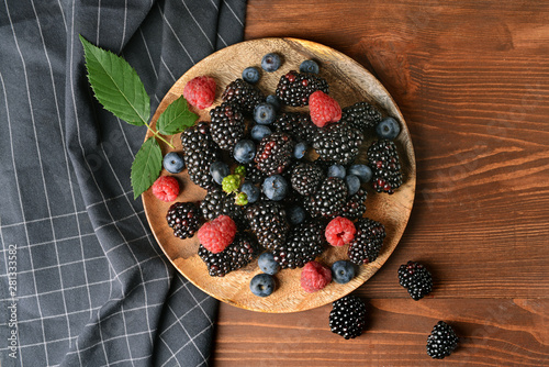Plate with tasty berries on wooden table Fototapeta
