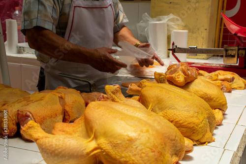 Fototapeta Pollería en mercado mexicano, con pollos crudos siendo partidos por el carnicero
