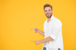 Leinwandbild Motiv Look there. Man pointing at copy space. Check this out. Man muscular handsome smiling unshaven guy on yellow background pointing finger. Advertising concept. Summer advertising. Advertising agency