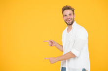 Look There. Man Pointing At Copy Space. Check This Out. Man Muscular Handsome Smiling Unshaven Guy On Yellow Background Pointing Finger. Advertising Concept. Summer Advertising. Advertising Agency