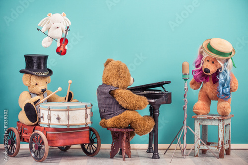 Teddy Bear toys music band: vocalist with colored hair, retro old microphone, bear in cylinder hat playing drum, flying angel with fiddle, grand piano player. Vintage nostalgia style filtered photo - 281339302