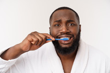 Portrait Of A Happy Young Dark-anm Brushing His Teeth With Black Toothpaste On A White Background.