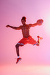 shirtless african american sportsman in red shorts jumping while playing basketball on pink and purple gradient background
