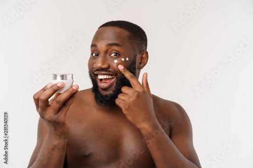 Obraz na plátně  Smiling afro man applying cream on his face