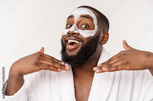 Poster Spa Young african-american guy applying face cream on white background. Portrait of a young happy smiling african man at studio. High fashion male model.