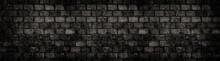 Old And Weathered Grungy Black Dark Concrete Block Brick Wall Texture Background Abandoned House With Holes And Cracks And Vignetting As Scary Large Panorama Wide Banner Background.