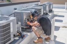 Hvac Technician Checking Controls On A Condenser