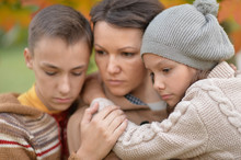 Close-up Portrait Of Sad Mother With Children Outdoors