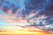 Heavenly summer background. Beautiful bright majestic dramatic evening sky at sunset or sunrise orange and blue with rays. The sun shines over the horizon against the backdrop of thunder clouds