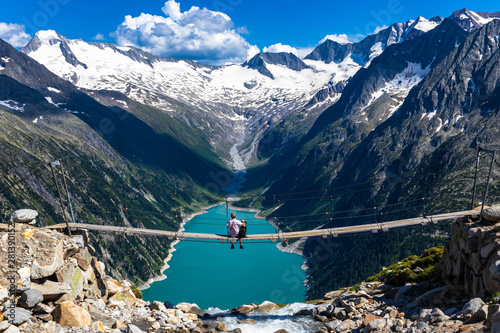 Hiker with dog looking at view of Schlegeispeicher from Olperer Hutte bridge - 281390152