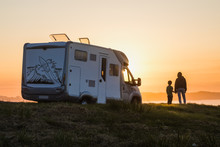Mother And Son Watching The Sunset With Their Motor Home At The Edge Of The Sea