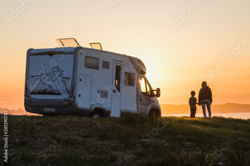 Fototapeta  mother and son watching the sunset with their motor home at the edge of the sea