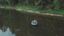 Aerial View Of Man In Coverall Fishing In The Rubber Boat On The River Near The Side With Plants, Shrubs And Trees In Summer Day. Stock Footage. Summer Fishing Season
