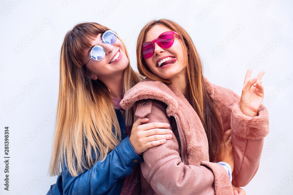 Fototapety, obrazy: Close up fashionable portrait couple of two cute girls best friends smiling and embracing on white wall background.Friends forever.Two cute lovely girl friends in blue and pink leather coats.