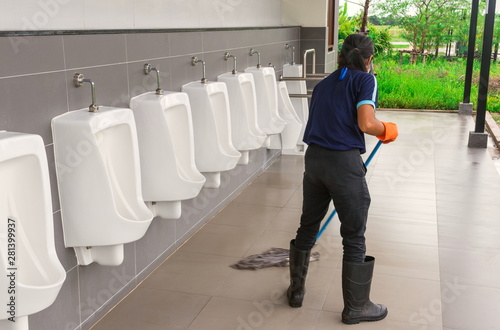 Photo The young cleaner woman is cleaning by mopping the floor in toilet and the urina