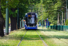 Blur, The Tram Goes On Rails In The Alley Of Trees. Eco-friendly Urban Public Transport. Urban Forestry, Protection Of The Environment.