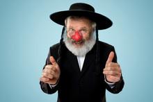 Portrait Of An Senior Jewish Man Celebrating Red Nose Day. Purim, Festival, Holiday, Celebration, Judaism, Religion, Human Emotions Concept. Old Man Smiling On Blue Studio Background.