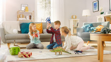 In The Living Room: Boy And Girl Playing With Toy Airplanes And Dinosaurs While Sitting On A Carpet. Sunny Living Room With Children Having Fun.