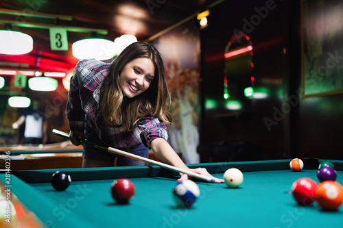 Foto Young happy girl having fun with billiard. Play and fun concept.