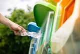 Fototapeta Kawa jest smaczna - Close up shot, hand putting twisted empty plastic drinking water bottle into recycle bin in public.