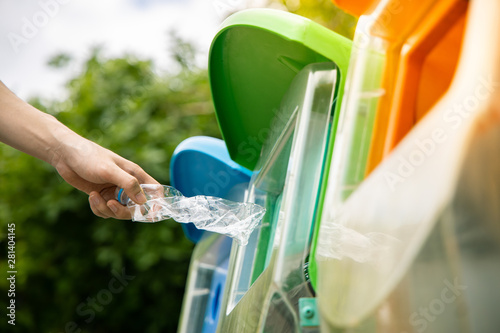 Close up shot, hand putting twisted empty plastic drinking water bottle into recycle bin in public.