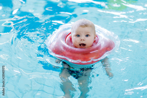 Obraz Cute little baby child learning to swim with swimming ring in an indoor pool - fototapety do salonu