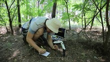 Caucasian Entomologist Studying A Small Anthill In The Forest Cheryl Magnifying Glass And Take Notes In His Notebook, Close-up