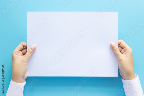 Fototapeta  close up hands holding  empty white blank letter paper size A4 for flyer or invitation mock up isolated on a blue background
