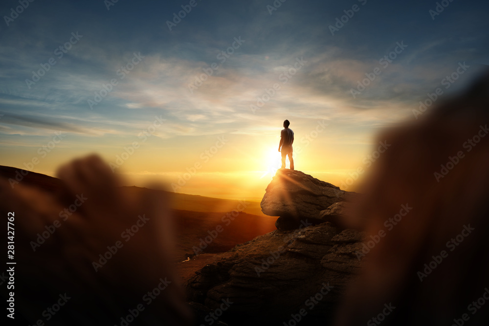 Fototapeta Leadership And Goals. A man standning on top of a mountain watching the sun set. Conceptual photo composite.