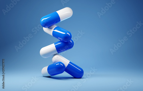 Photo  A stack of antibiotic pill capsules on a blue background