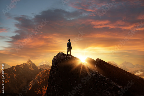 Fototapeta A man standing on top of a mountain as the sun sets. Goals and achievements concept photo composite. obraz