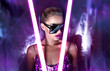canvas print picture - Portrait of a beautiful young tanned girl in big sunglasses in a pink shiny dress in the studio on a silver background with a pink and purple hue. Glowing fluorescent lamps in the face.