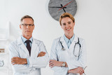 Fototapeta Panels - doctor in glasses standing with crossed arms near cheerful colleague in clinic