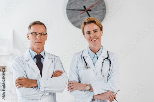 Fototapeta doctor in glasses standing with crossed arms near cheerful colleague in clinic