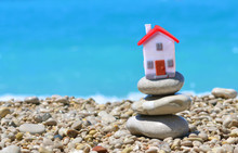 Cottage Lodge By The Sea Concept With Little Toy House And Pebbles