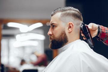 Hairdresser with a client. Man with a beard. Guy in a barbershop