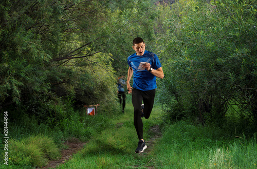 Orienteering. Man runs with map and compass