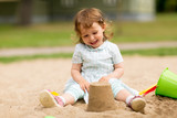 Fototapeta Panels - childhood, leisure and people concept - little baby girl plays with toys in sandbox