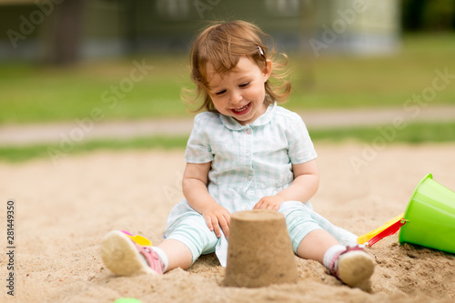 childhood, leisure and people concept - little baby girl plays with toys in sandbox - 281449350