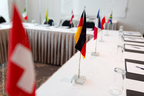 business, corporate and interior concept - flags on table in boardroom at international conference
