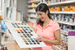 canvas print picture Woman with paint color swatch in specialized store looks at the different shades of color, customer or employee