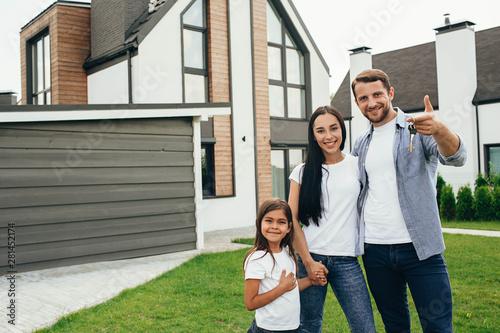 Fotografia, Obraz Happy heteroseksual family standing near their new house